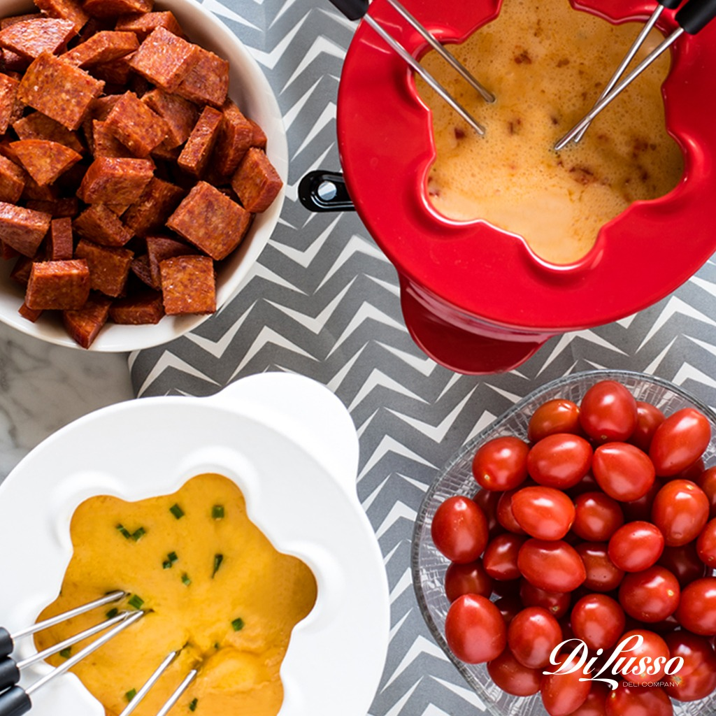 Two types of Di Lusso fondue with hard salami and cherry tomatoes