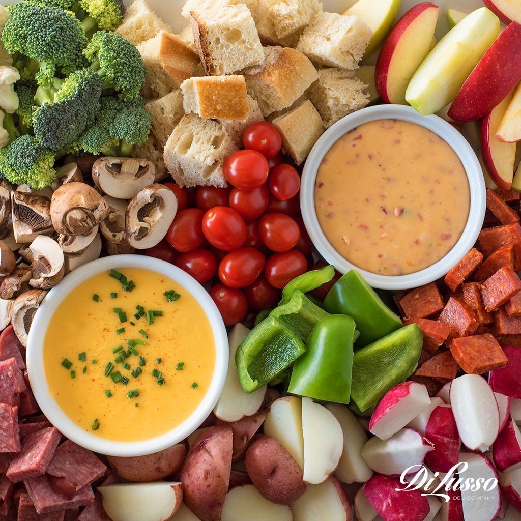2_Closeup of two cheese fondues with variety of meat and vegetables to dip