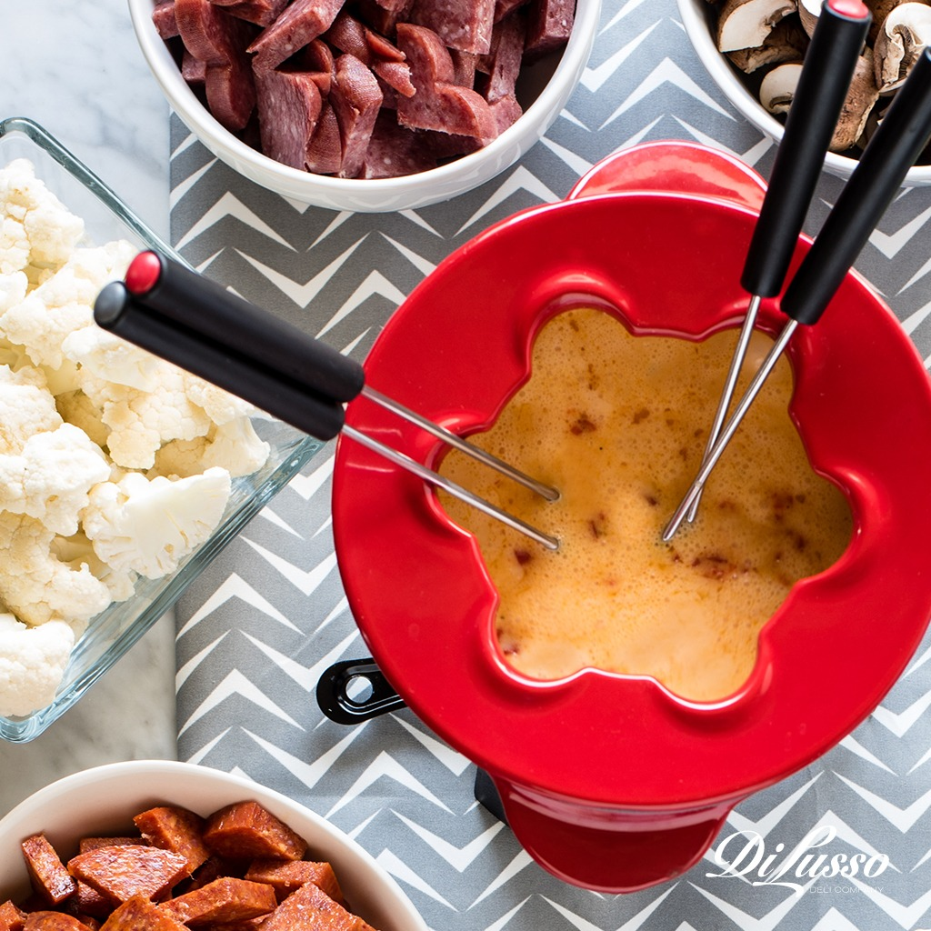 Cheese Fondue with multiple skewers, and meat and vegetables to dip